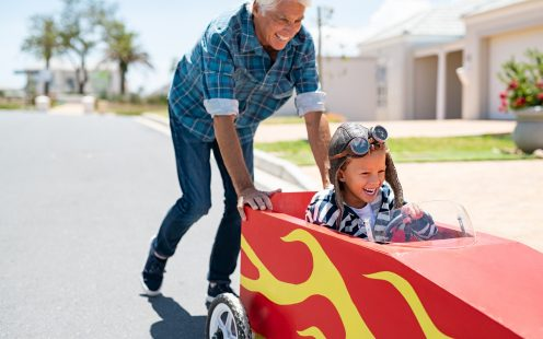 Senior grandfather helping grandson ride on kids toy car. Happy old man pushing car while boy driving on street. Grandparent playing with little boy on gokart.